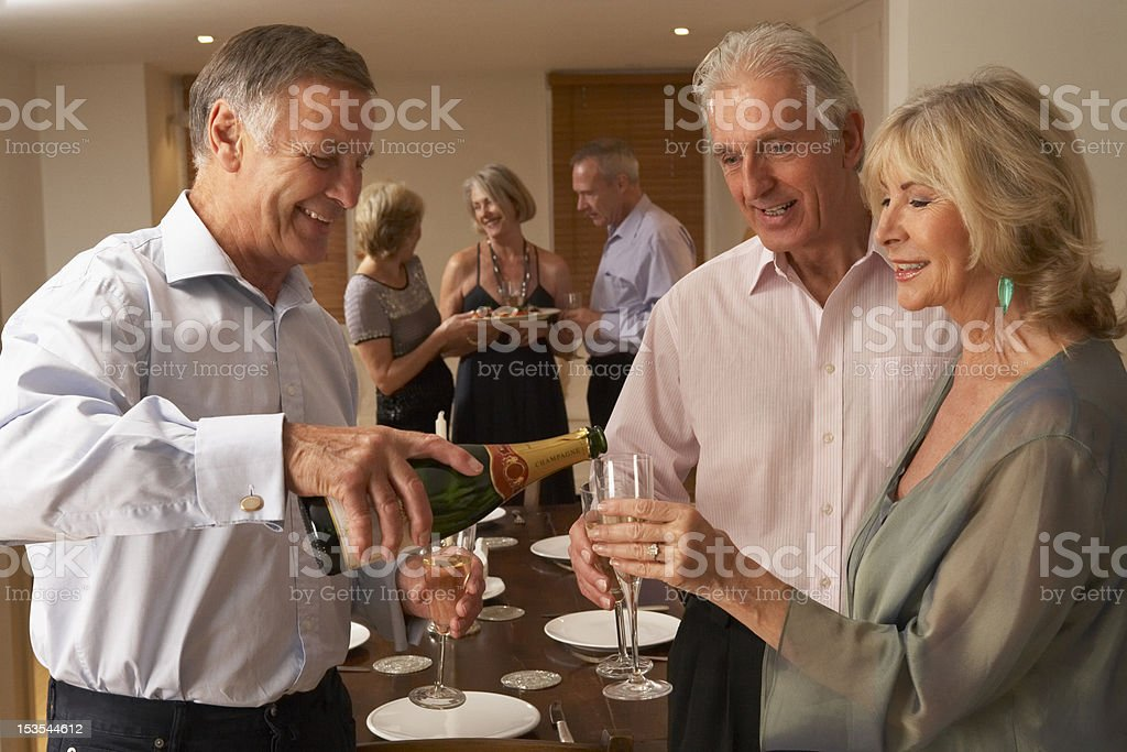 Man Serving Champagne To His Guests At A Dinner Party stock photo