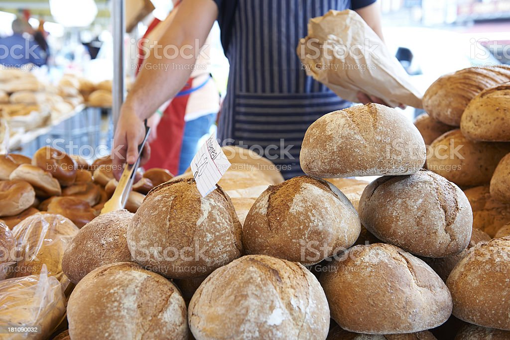 Man Serving On Bread Stall At Outdoor Market royalty-free stock photo