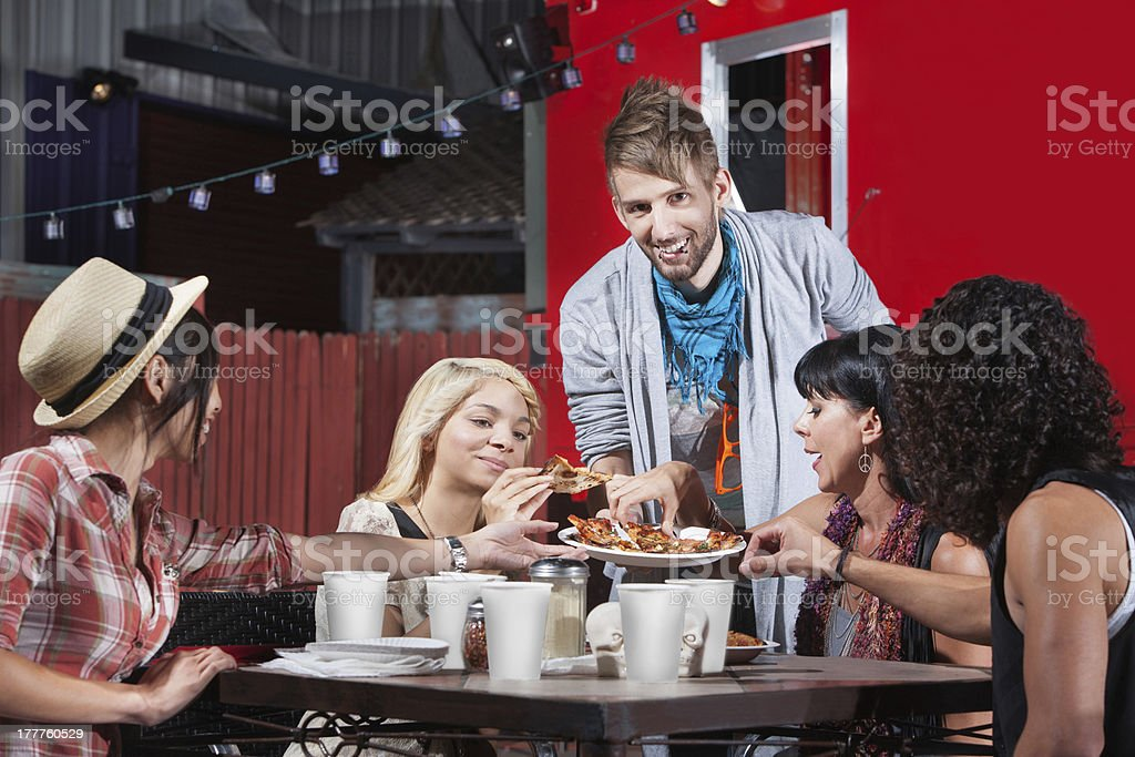 Man Serving Pizza to Friends royalty-free stock photo