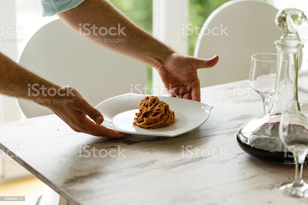 Man serving vegetarian spaghetti stock photo