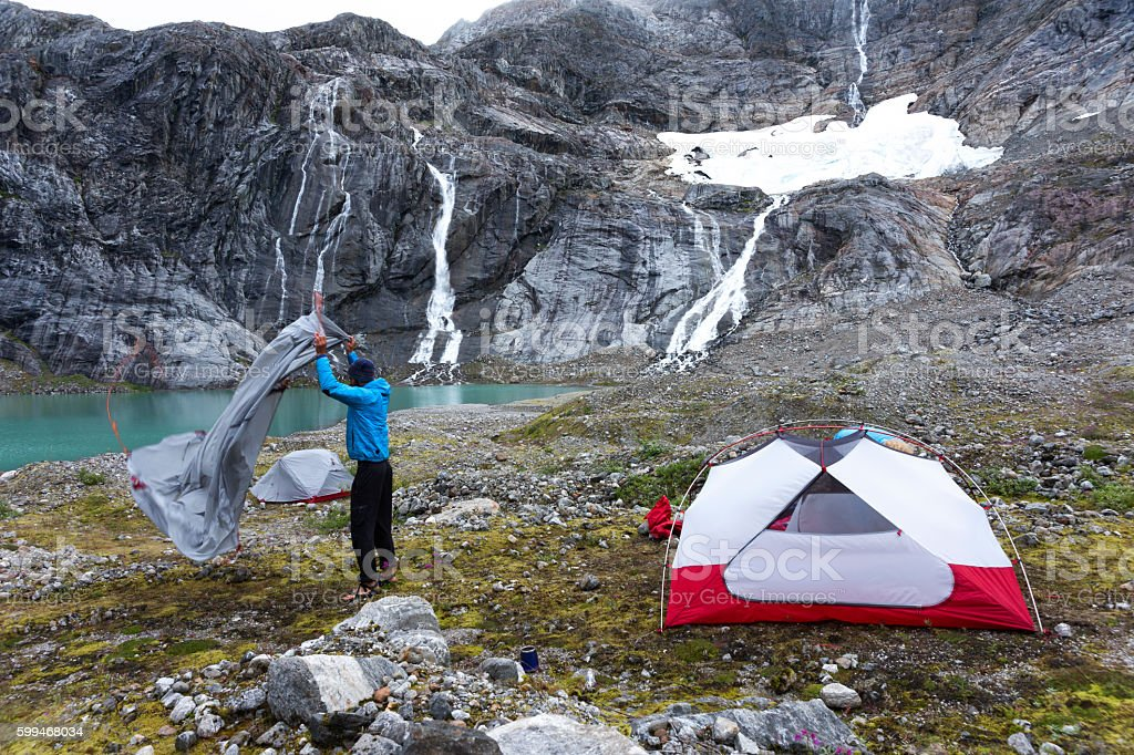Man sets up red tent near waterfall on glacier stock photo