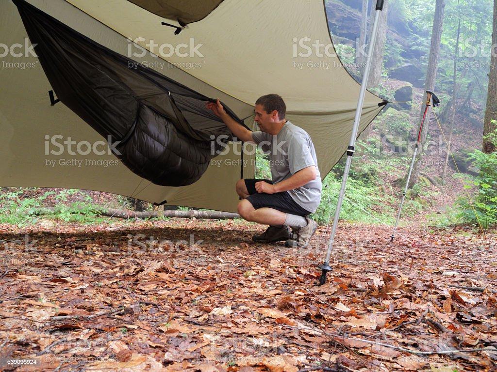 Man setting up camping hammock under tarp stock photo