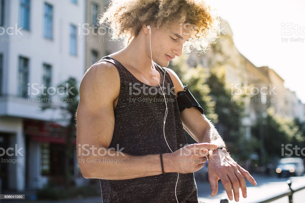 Man setting up smartwatch for running stock photo