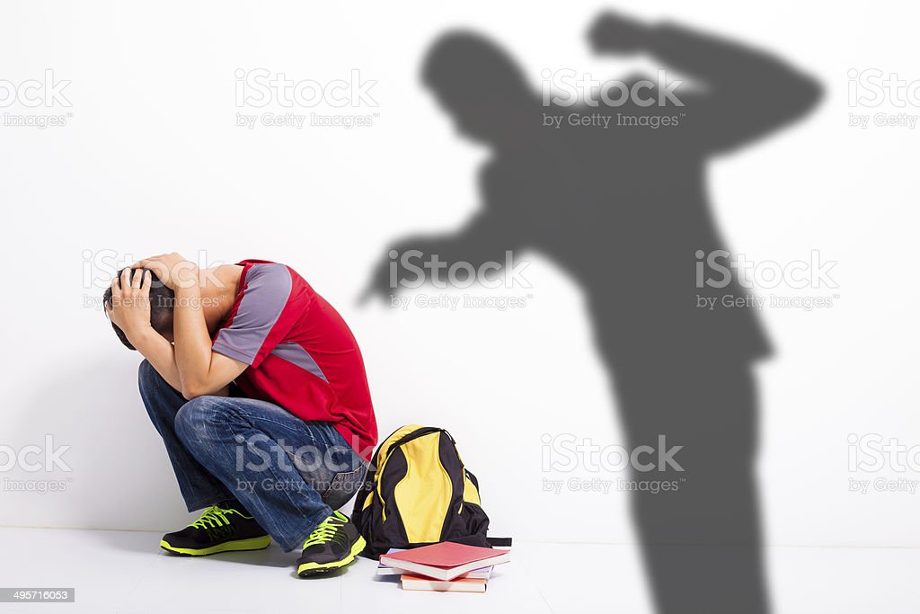 Man shadow attack   to terrified student with a fist stock photo