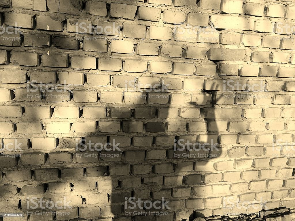 Man shadow on brick wall stock photo