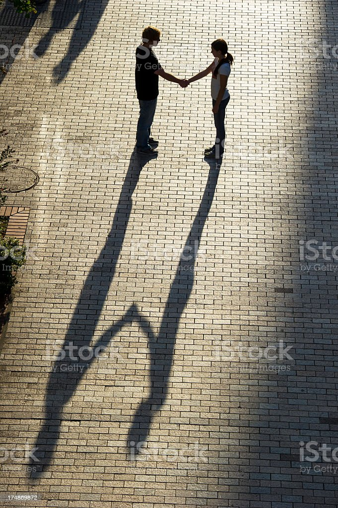 A man shakes a woman's hands, casting a long shadow stock photo