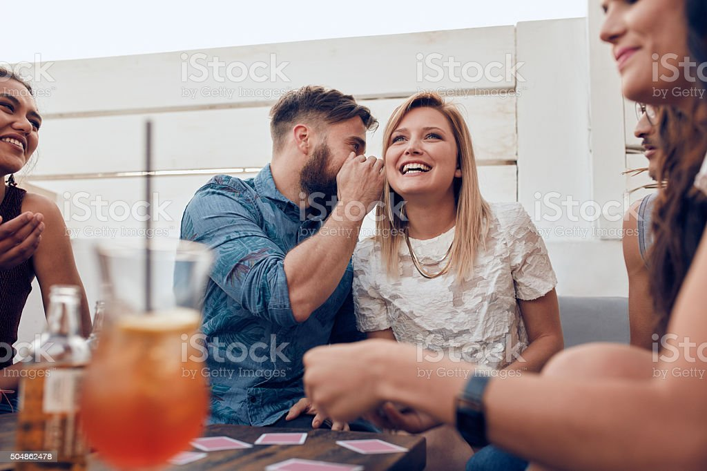 Man sharing a secret with woman in a party stock photo
