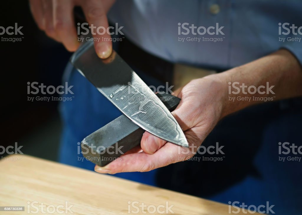 Man sharpens kitchen knife stock photo