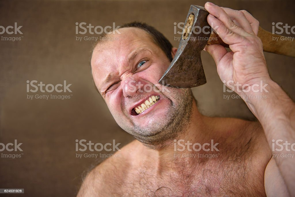 Man shaves with an ax stock photo