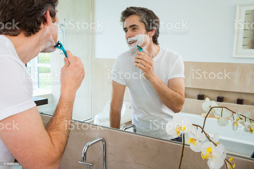 Man shaving at bathroom mirror stock photo