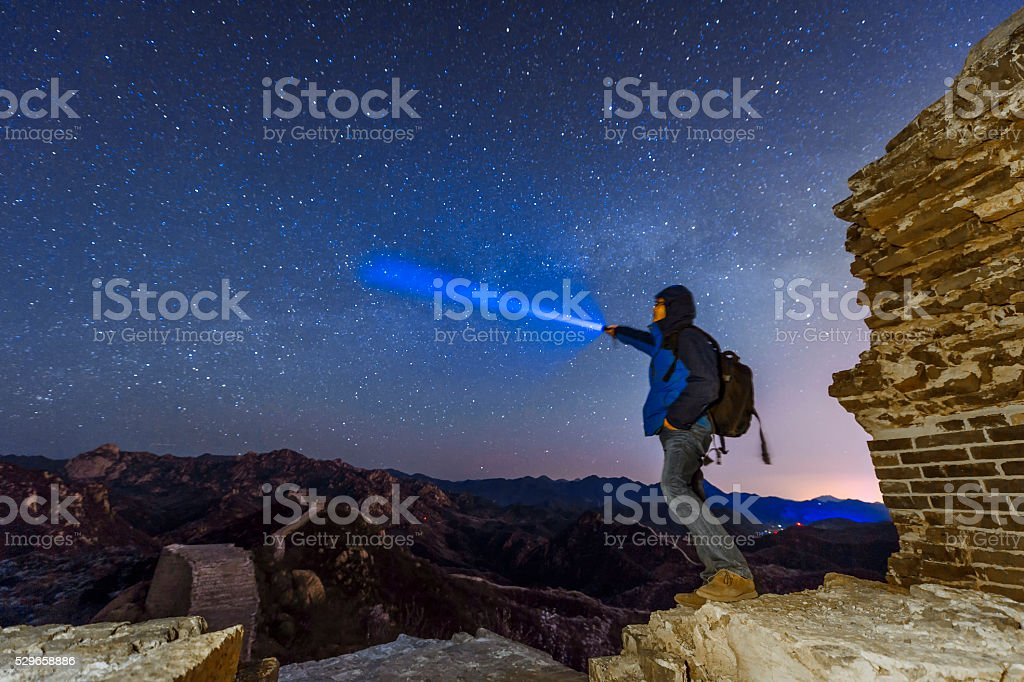 Man Shining a flashlight on The great wall at night stock photo