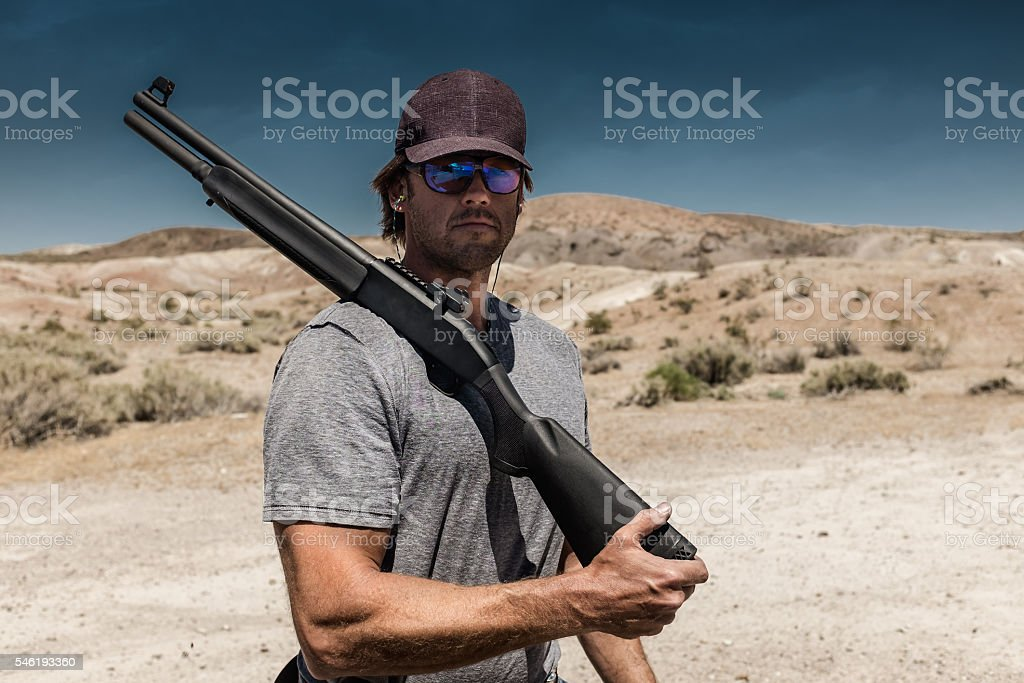 Man Shooting A 12 Gauge Shotgun stock photo