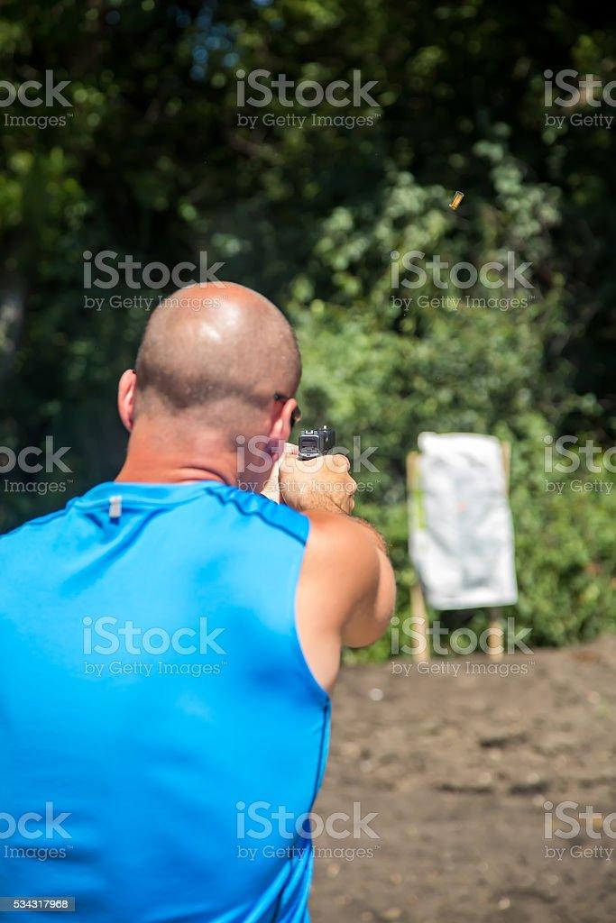 Man Shooting Handgun at Homemade Target Outside stock photo