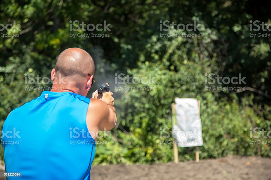 Man Shooting Handgun at Homemade Target Outside stock photo