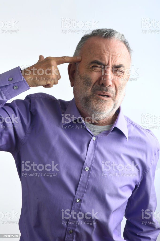 man shooting with a finger on his head stock photo