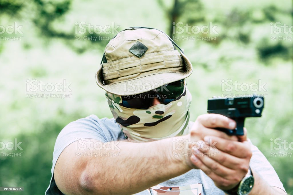 A man shoots a pistol. He looks at us stock photo
