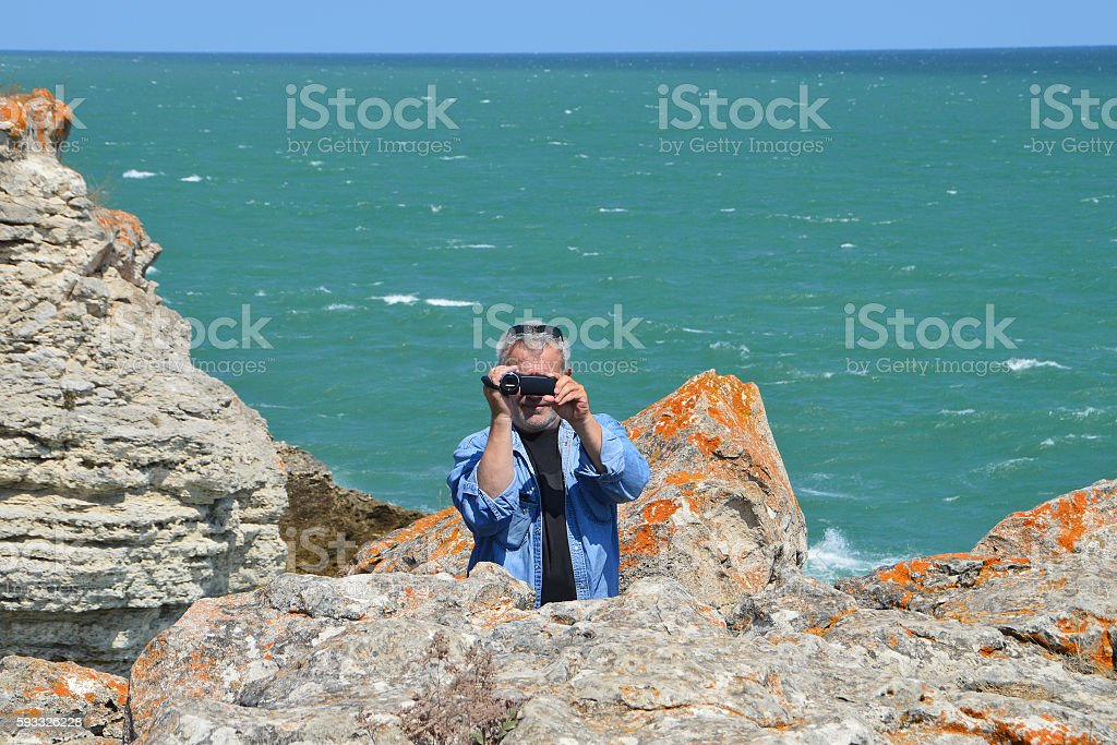 Man shoots video on the cliffs above the see stock photo