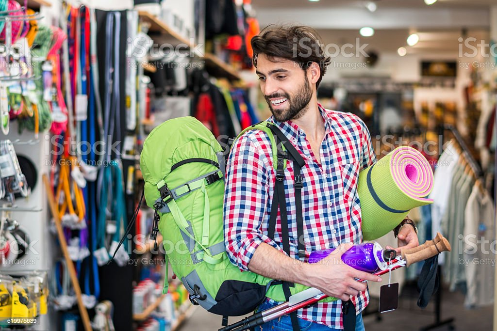 Man shopping outdoor equipment in sports store stock photo