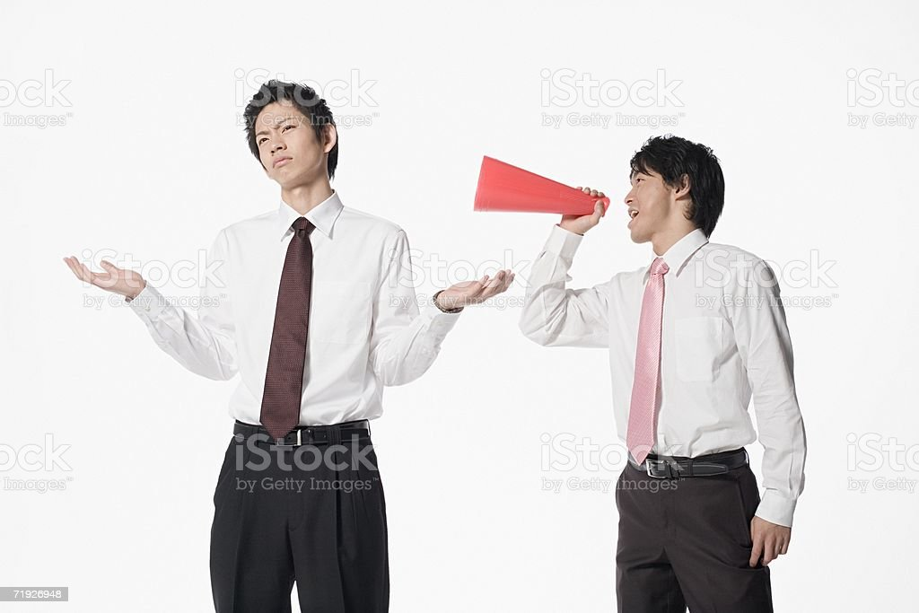 Man shouting at colleague with megaphone royalty-free stock photo