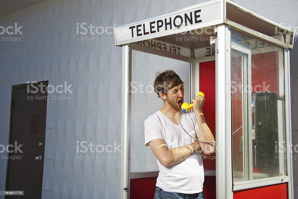 Man shouts into the phone in a phonebooth royalty-free stock photo