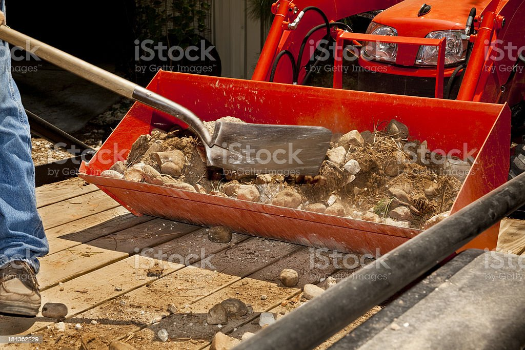 Man shoveling rock into tractor bucket royalty-free stock photo