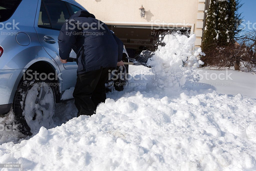 Man shoveling snow away from his car's tires in driveway. stock photo