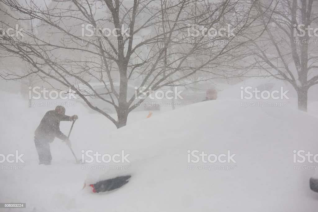 Man shoveling snow from driveway in blizzard stock photo