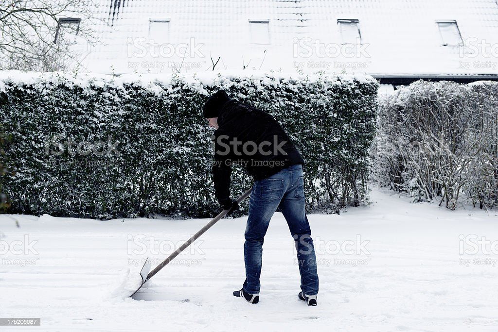 Man shoveling snow on a road royalty-free stock photo