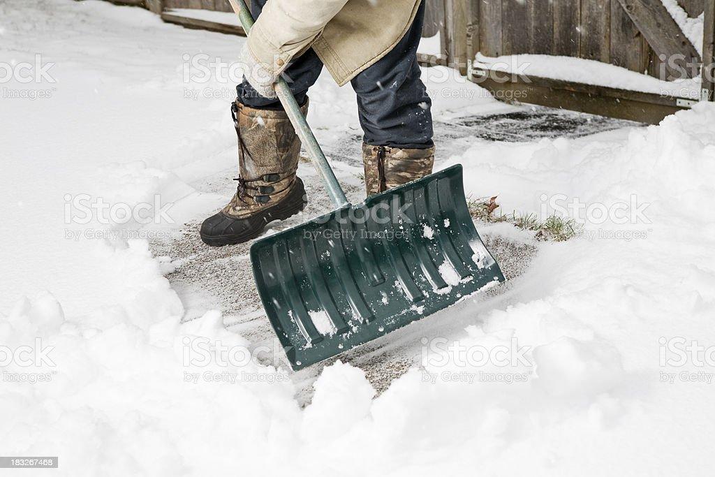 Man Shovels Snow from Sidewalk royalty-free stock photo