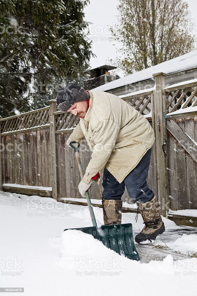 Man Shovels Snow from Sidewalk royalty-free stock photo
