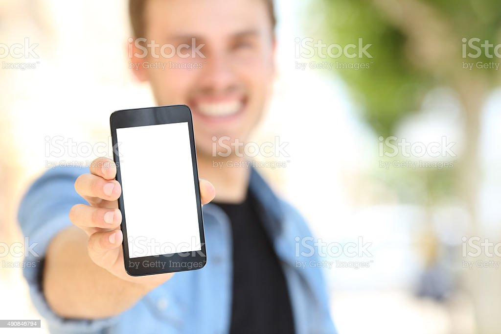 Man showing a blank phone screen in the street stock photo