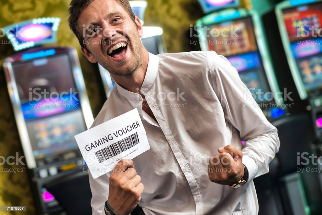 Man Showing a Gaming Voucher. Slot Machine on the background. royalty-free stock photo