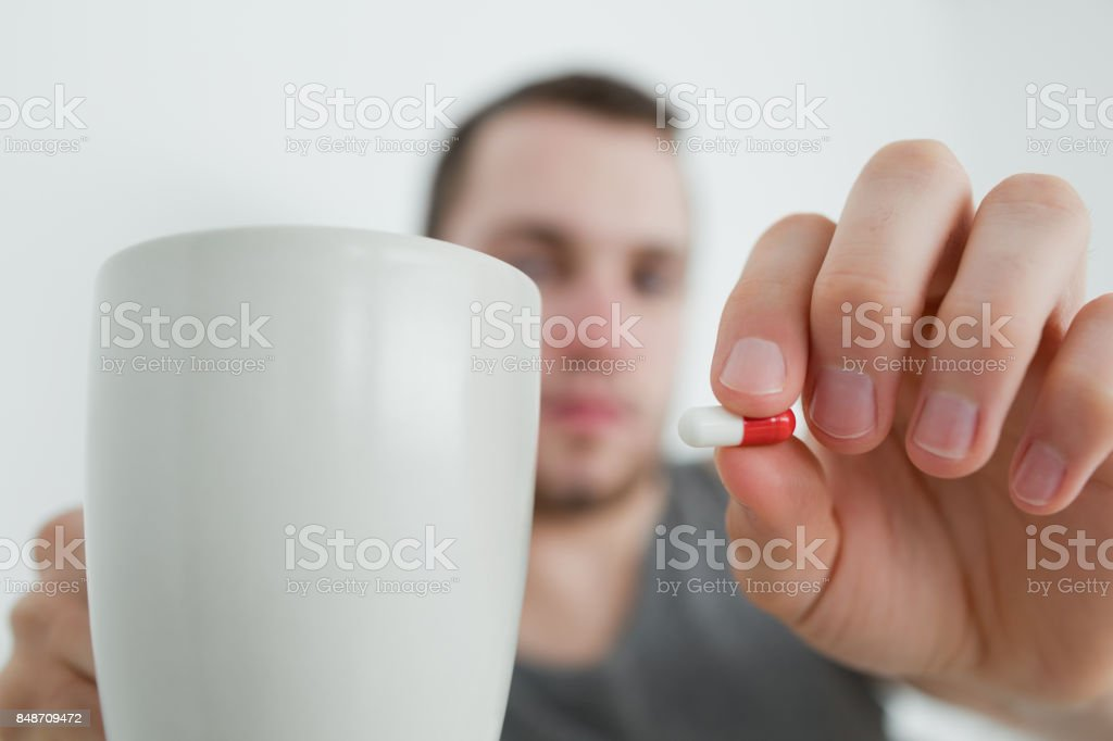 Man showing a pill and and a mug stock photo