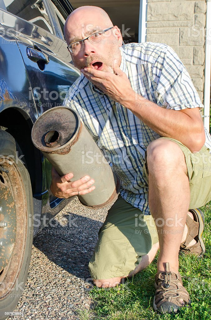 Man showing his muffler fallen from his rusty car stock photo