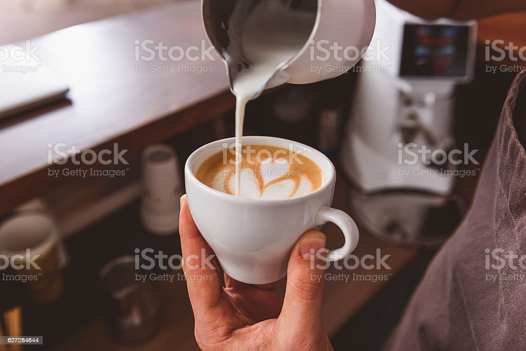 man showing how to make coffee art stock photo
