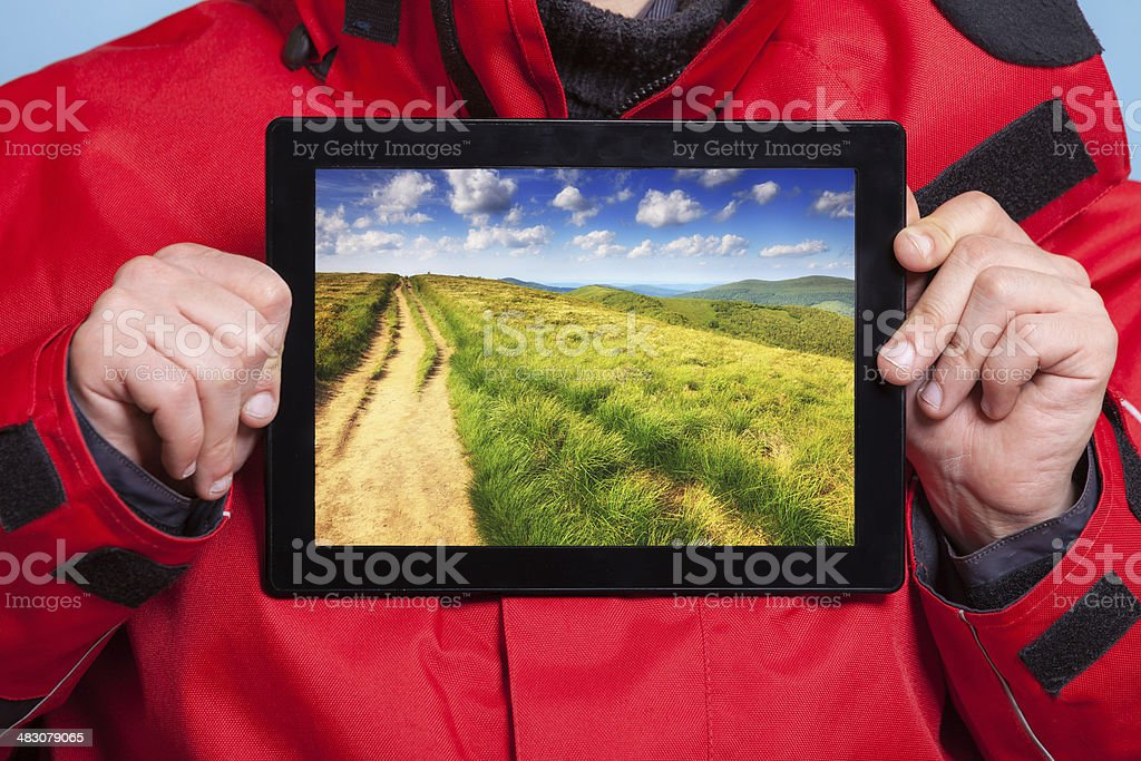 Man showing mountains on tablet. Travel royalty-free stock photo