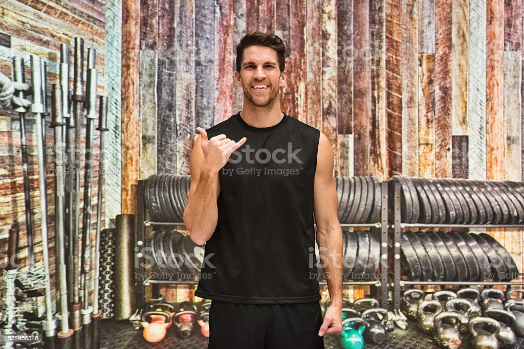 Man showing shaka sign in gym stock photo