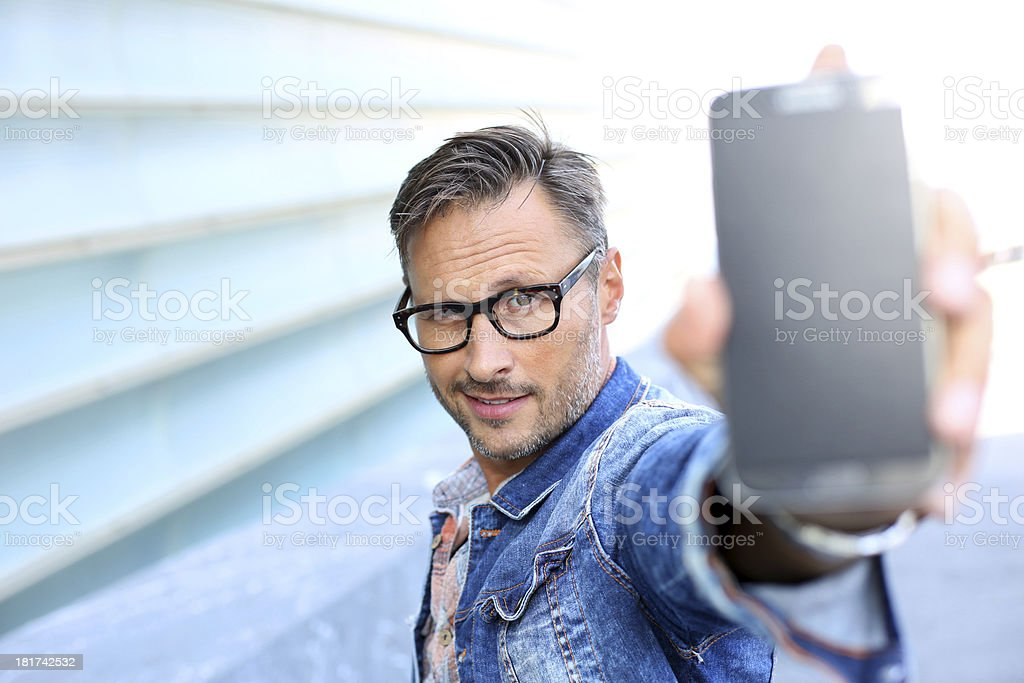 Man showing smartphone to camera royalty-free stock photo