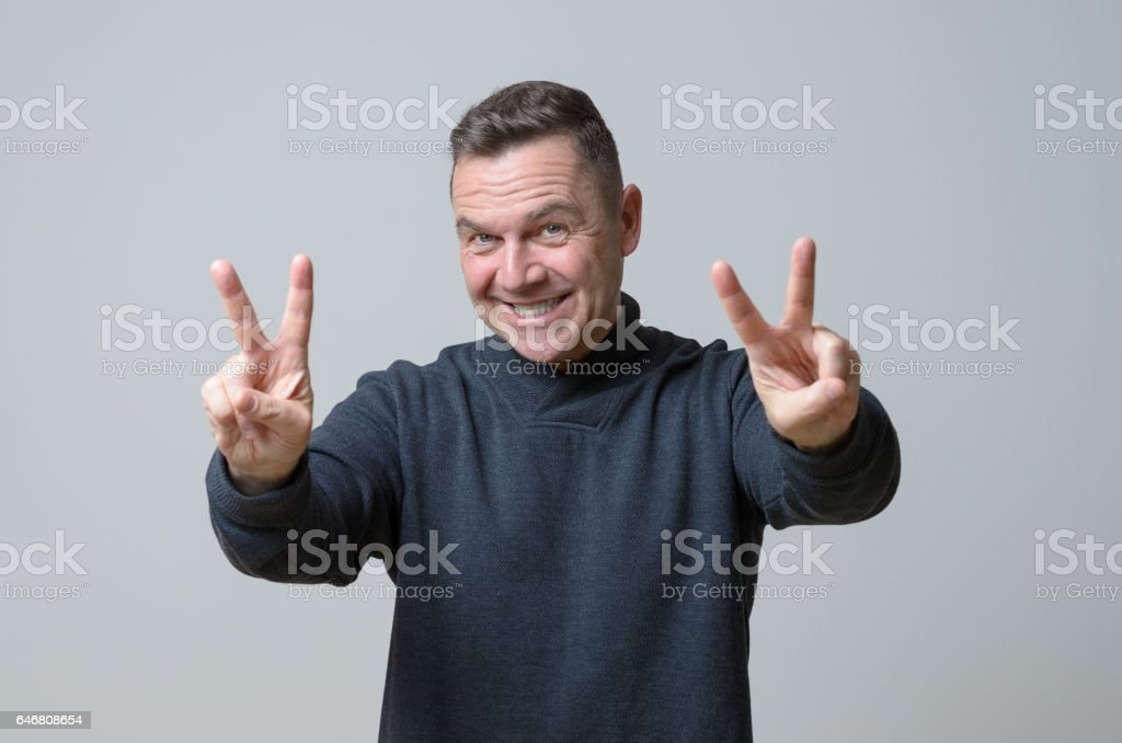 Man showing V signs stock photo
