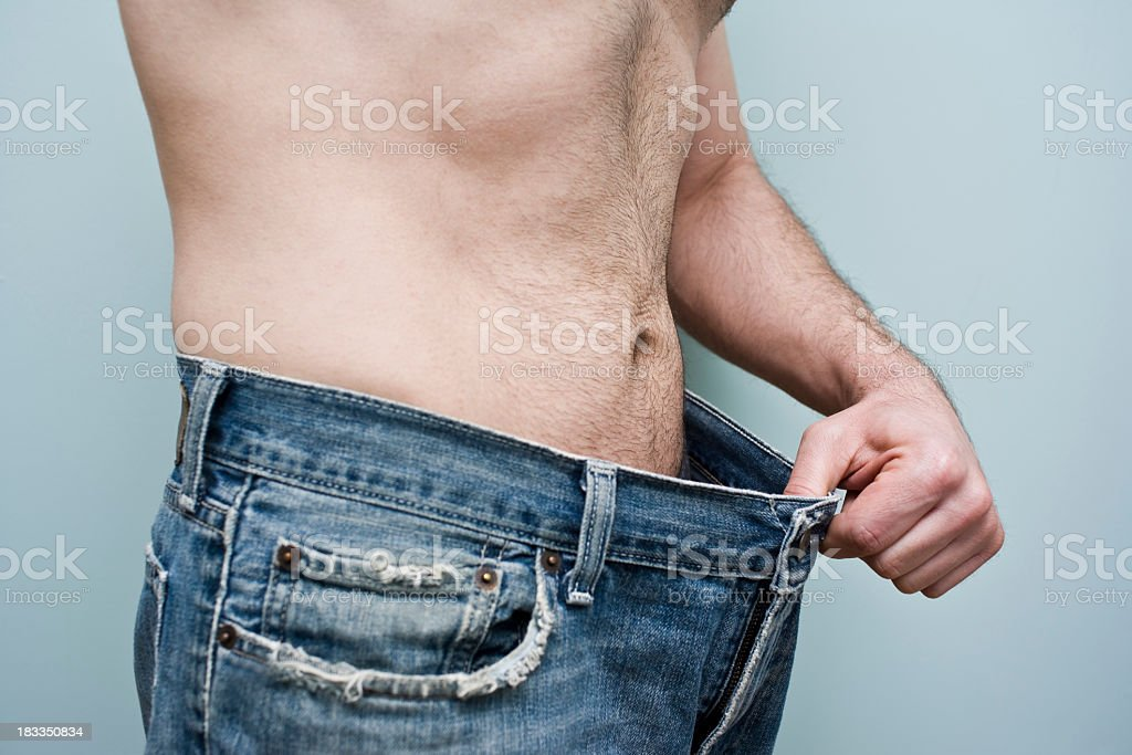 Man showing weight loss by showing his loose pants stock photo