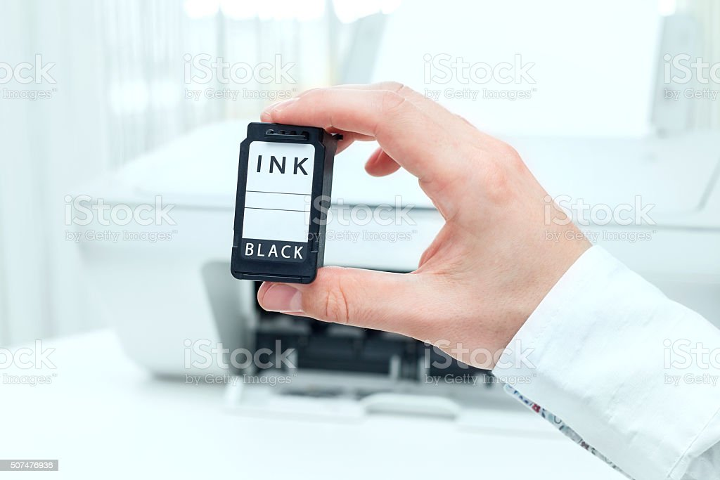 Man shows black ink cartridge from white printer stock photo