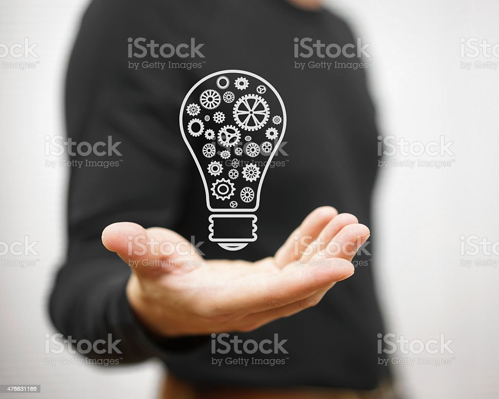 Man shows light bulb with gear inside stock photo