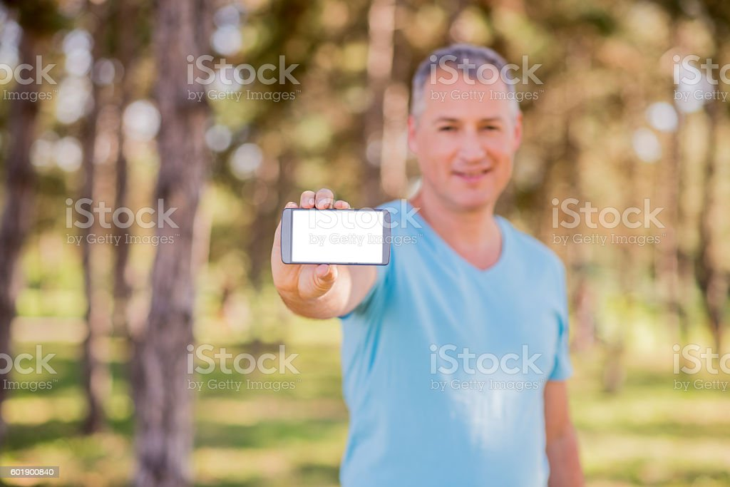 Man shows mobile smart phone. Shot with third-person view stock photo