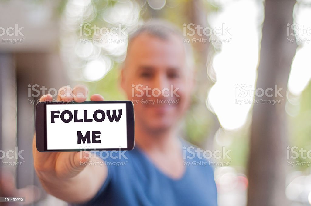 Man shows mobile smartphone blank screen with FOLLOW ME option stock photo