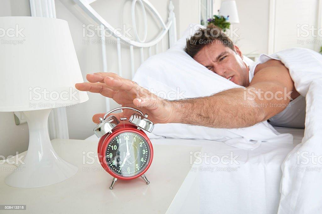 Man shutting off alarm clock stock photo