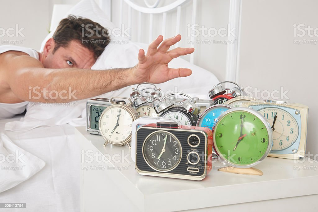 Man shutting off alarm clocks stock photo