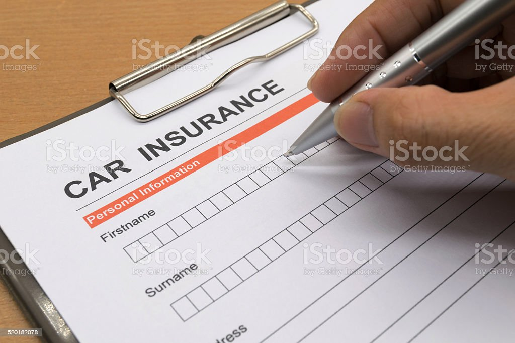 man signing a car insurance policy stock photo
