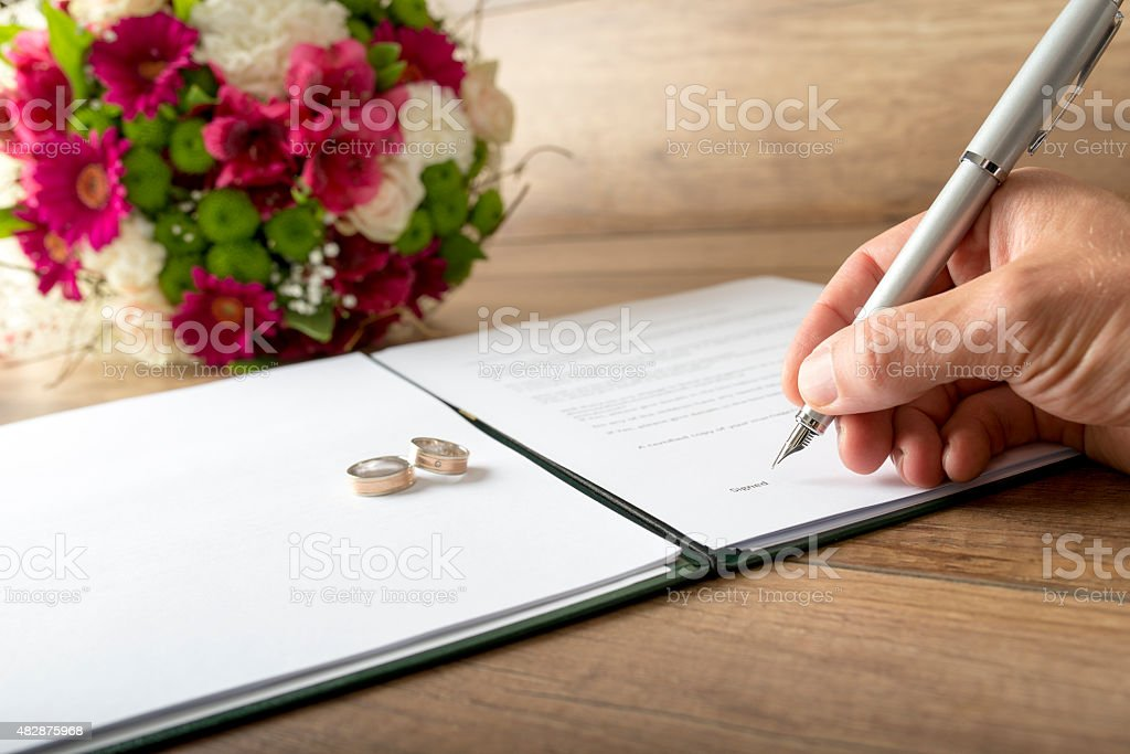 Man signing a marriage register stock photo