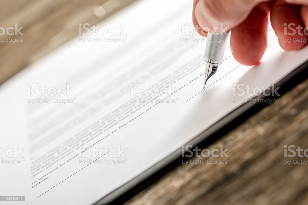 Man signing business document, subscription form or insurance pa stock photo