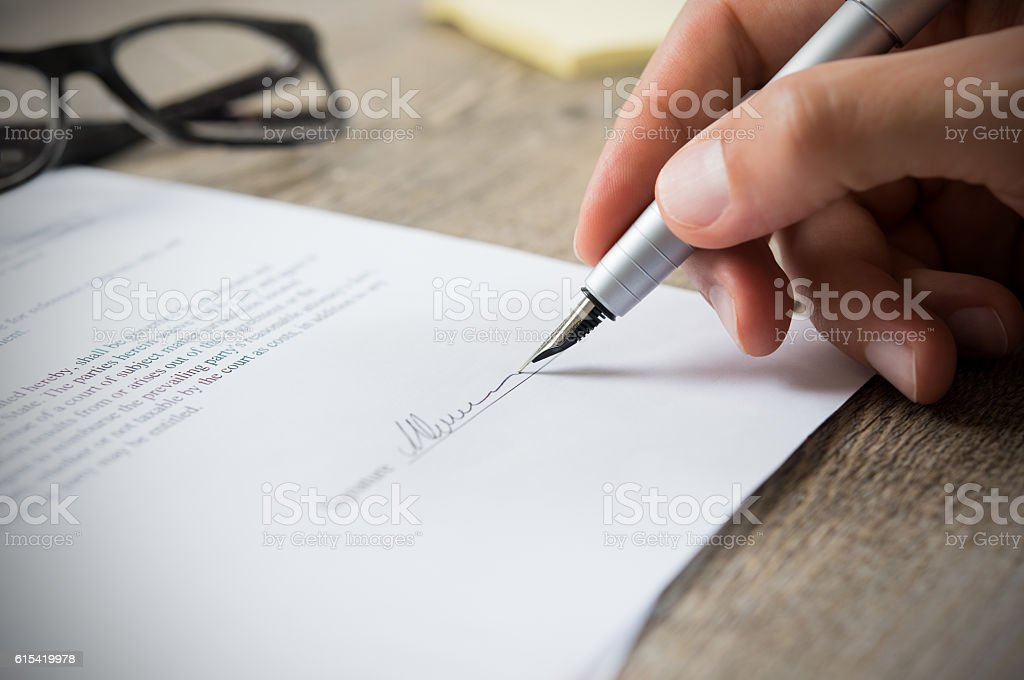 Man signing contract stock photo